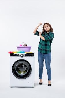 흰색 벽에 세탁기와 샴푸가 있는 전면 보기 젊은 여성