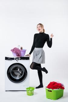 Vista frontale giovane donna con lavatrice e vestiti sporchi sul muro bianco Foto Gratuite