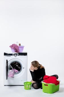 Vista frontale della giovane donna con la lavatrice che piega i vestiti sporchi sul muro bianco