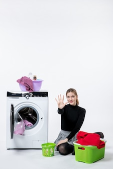 Front view of young female with washing machine folding dirty clothes on white wall