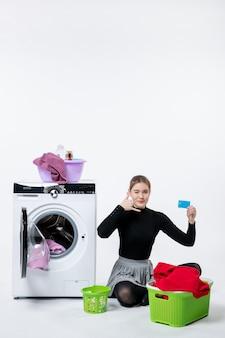 Vista frontale della giovane donna con la lavatrice che tiene la carta bancaria sulla parete bianca
