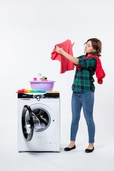 Vista frontale della giovane donna con la lavatrice che prepara i vestiti per il lavaggio sul muro bianco