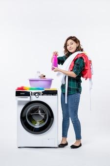 Vista frontale della giovane donna con la lavatrice che prepara i vestiti sulla parete bianca