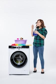 Vista frontale della giovane donna con la lavatrice che prepara la polvere liquida sulla parete bianca