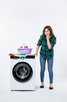 Front view young female with washing machine and shampoos on a white wall