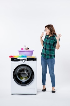Front view young female with washing machine and shampoos on white wall