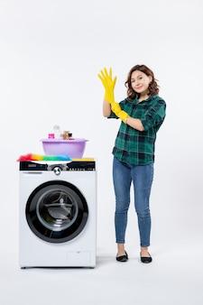 Vista frontale di una giovane donna con lavatrice che indossa guanti gialli su un muro bianco
