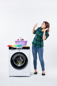Vista frontale della giovane donna con lavatrice sul muro bianco