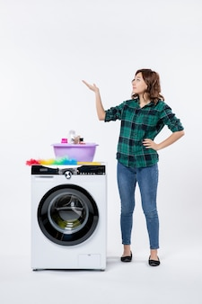 Front view of young female with washing machine on white wall