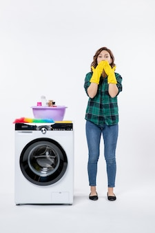 Front view of young female with washing machine in yellow gloves on the white wall