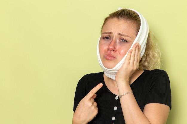Вид спереди молодая женщина с белым полотенцем вокруг головы, чувствуя себя очень больной и больной от зубной боли на зеленой стене болезнь болезни девушка здоровья