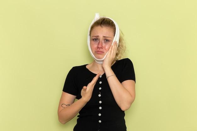 녹색 벽 질병 질병 여성 건강에 치통으로 매우 아프고 아픈 느낌이 그녀의 머리 주위에 흰색 수건으로 전면보기 젊은 여성