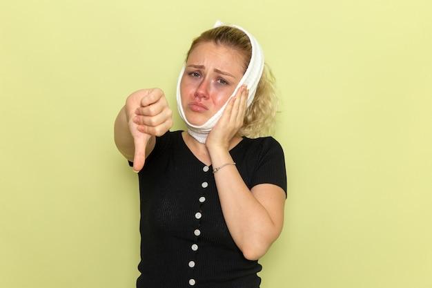 녹색 벽 질병 질병 여성 건강 소녀에 치통에서 매우 아프고 아픈 느낌 그녀의 머리 주위에 흰색 수건으로 전면보기 젊은 여성