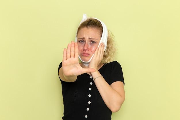 녹색 벽 질병 질병 여성 건강 소녀에 슬퍼 치통에서 매우 아프고 아픈 느낌 그녀의 머리 주위에 흰색 수건으로 전면보기 젊은 여성