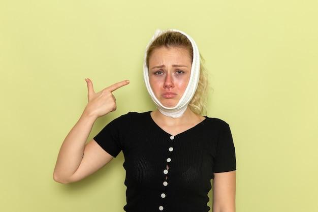 Giovane donna di vista frontale con un asciugamano bianco intorno alla testa che si sente molto malato e malato di mal di denti sulla ragazza di salute femminile malattia malattia scrivania verde