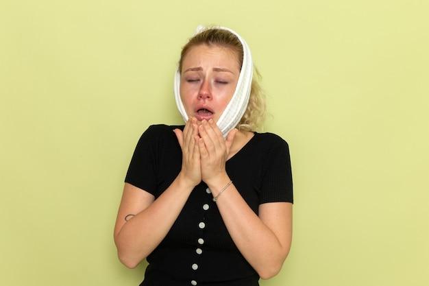 Giovane femmina vista frontale con un asciugamano bianco intorno alla testa sensazione di malessere e mal di denti starnuti sul muro verde malattia malattia femminile salute ragazza