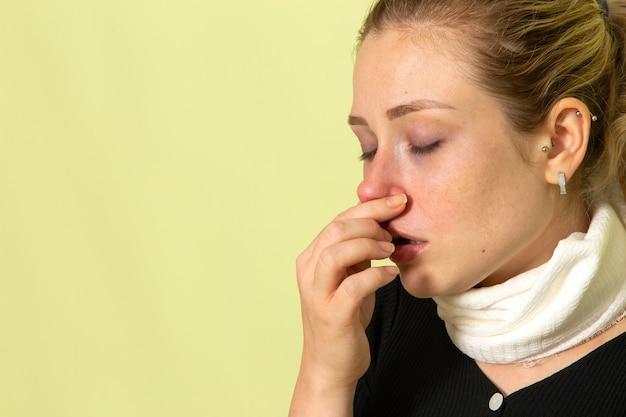 Вид спереди молодая женщина с белым полотенцем вокруг горла, чувствуя себя очень больной и больной, чистит нос на светло-зеленом столе