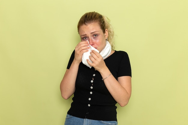 Вид спереди молодая женщина с белым полотенцем вокруг горла, чувствуя себя очень больной и больной, чистит нос на светло-зеленой стене болезнь болезнь девушка здоровье девушка