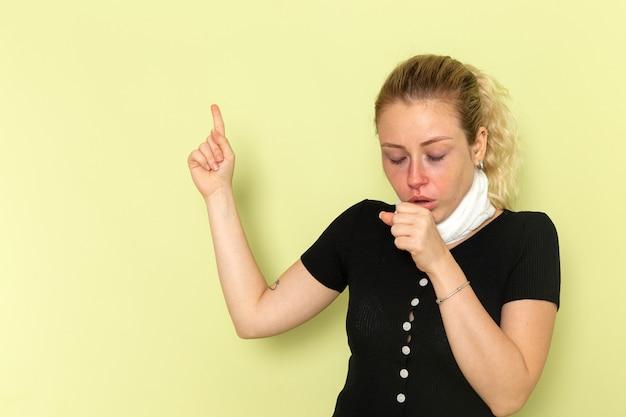 Вид спереди молодая женщина с белым полотенцем вокруг горла, чувствуя себя очень больной и больной, кашляет на светло-зеленом столе.