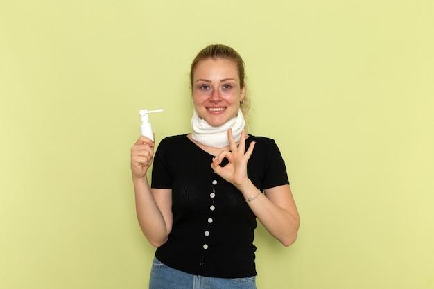 正面図若い女性の喉の周りに白いタオルが非常に気分が悪く、薄緑色の机に喉のスプレーを持って病気になっている病気の女性の健康上の病気
