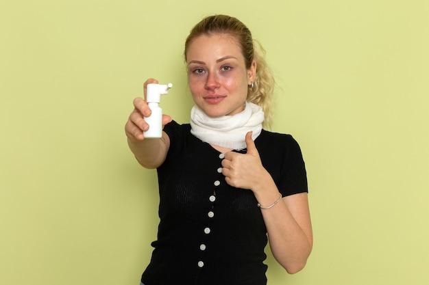 녹색 책상 질병 질병 여성 건강에 매우 아프고 아픈 목 스프레이를 들고 그녀의 목 주위에 흰색 수건으로 전면보기 젊은 여성