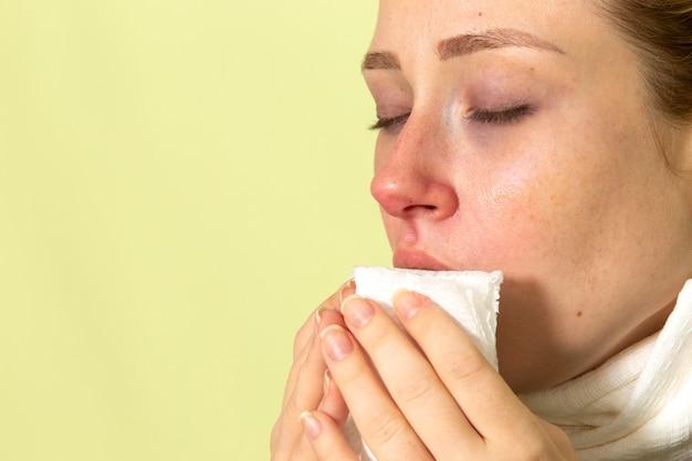 밝은 녹색 벽 질병 질병 여성 건강에 매우 아프고 아픈 재채기를 느끼는 그녀의 목 주위에 흰색 수건을 가진 전면보기 젊은 여성