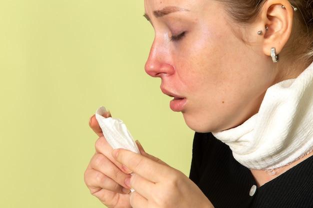 彼女の喉の周りに白いタオルを持った正面図若い女性は非常に気分が悪く、緑の壁の病気の病気の女性の健康の女の子に居眠りしている病気