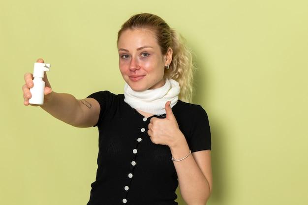 Giovane femmina di vista frontale con l'asciugamano bianco intorno alla sua gola che si sente molto malato e malato che tiene spray per la gola sulla salute femminile malattia malattia scrivania verde