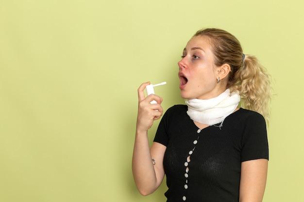 Giovane femmina di vista frontale con l'asciugamano bianco intorno alla sua gola che si sente molto male e malato usando lo spray sulla salute femminile di malattia di malattia della parete verde