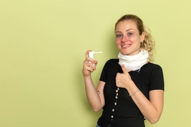Giovane femmina di vista frontale con l'asciugamano bianco intorno alla sua gola che si sente molto male e malato usando lo spray per la gola sulla salute femminile di malattia di malattia del muro verde