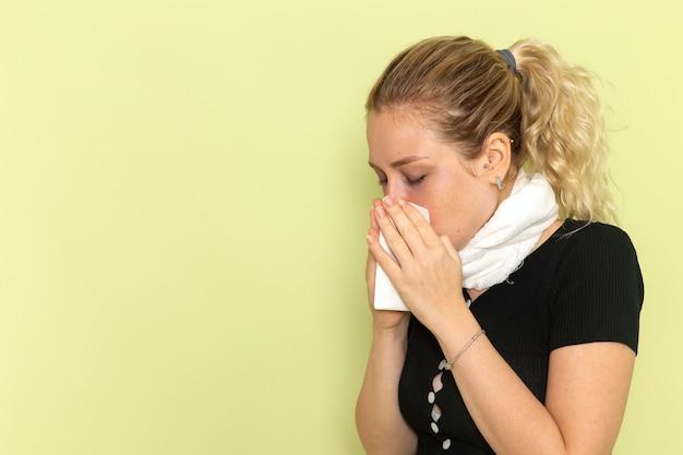 녹색 벽 질병 질병 여성 색상 건강에 그녀의 코를 청소 매우 아프고 아픈 느낌 그녀의 목 주위에 흰색 수건으로 전면보기 젊은 여성