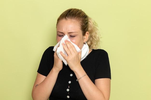 Вид спереди молодая женщина с белым полотенцем вокруг горла чувствует себя очень больной и плохо чистит нос на светло-зеленой стене болезнь болезнь женское здоровье