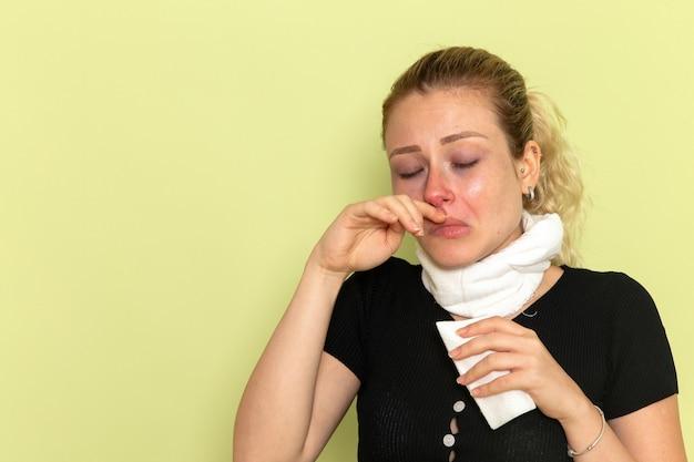 녹색 벽 질병 질병 여성 색상 건강에 매우 아프고 아픈 청소 코를 느끼는 그녀의 목 주위에 흰색 수건으로 전면보기 젊은 여성