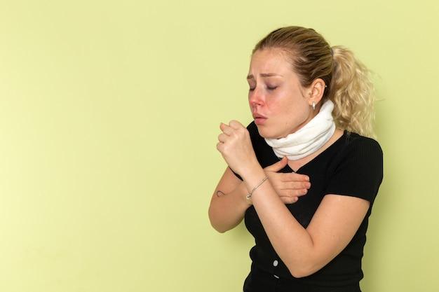 Вид спереди молодая женщина с белым полотенцем вокруг горла, чувствуя себя очень больным и плохо кашляющим на зеленой стене, болезнь, болезнь, женское здоровье