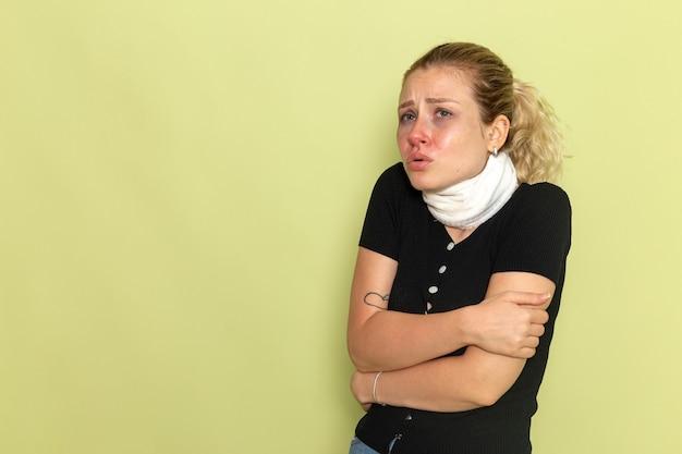 Вид спереди молодая женщина с белым полотенцем вокруг горла, чувствуя себя очень больным и больным, дрожит на зеленой стене.