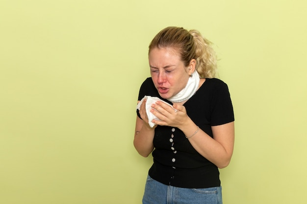 Front view young female with white towel around her throat feeling very sick and ill sneezing on light-green wall illness sickness female health girl