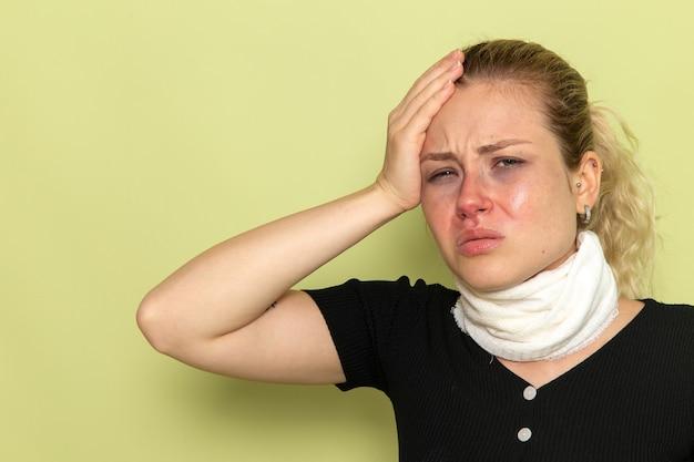 Giovane femmina di vista frontale con l'asciugamano bianco intorno alla sua gola che si sente molto malato e malato che tocca la sua testa sulla salute di colore femminile di malattia di malattia della parete verde