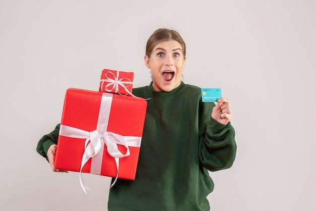 クリスマスプレゼントと銀行カードを持つ若い女性の正面図