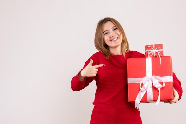 Вид спереди молодая женщина с рождественскими подарками