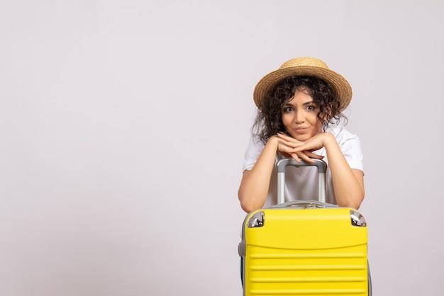 Вид спереди молодая женщина с желтой сумкой, готовящаяся к поездке на белом фоне, цвет солнца, рейс, самолет, отдых, туристический рейс, отпуск
