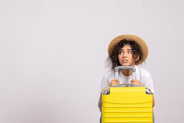 Вид спереди молодая женщина с желтой сумкой, готовящаяся к поездке на белом фоне, цвет солнца, отдых, отдых, туристический рейс, отпуск