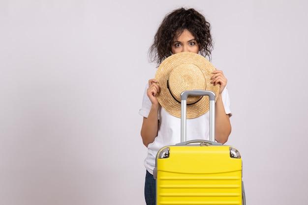 白い背景に旅行の準備をしている黄色いバッグを持つ若い女性の正面図旅行休暇の飛行機の航海の色