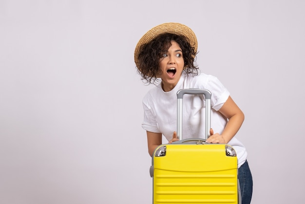 白い背景に旅行の準備をしている黄色いバッグを持つ若い女性の正面図旅行休暇飛行機航海色残り