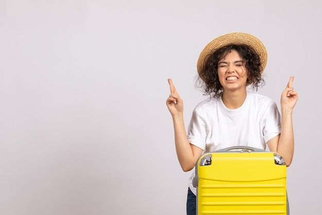Front view young female with yellow bag preparing for trip crossing her fingers on white background color vacation flight tourist plane rest voyage