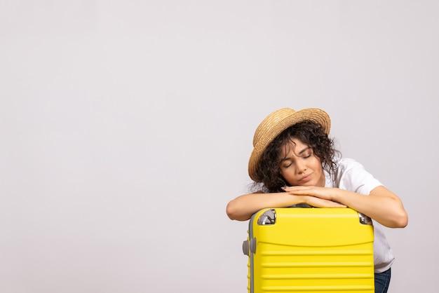 Vista frontale giovane donna con borsa gialla che si prepara per il viaggio e si sente stanca su sfondo bianco colore viaggio vacanza aereo sole riposo volo turistico