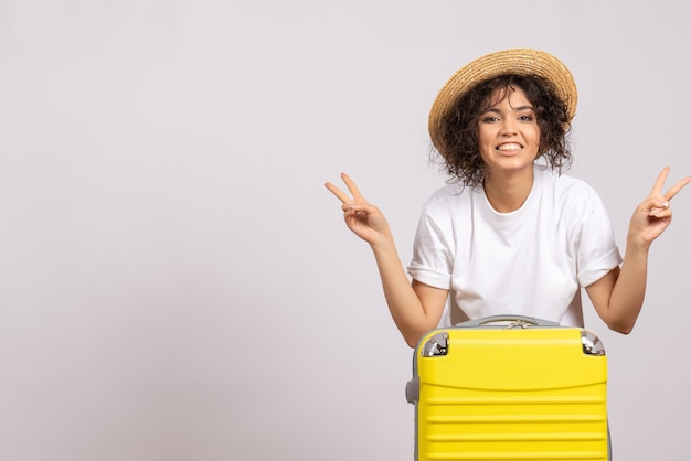 Front view young female with yellow bag preparing for trip on a white background color flight rest voyage plane tourist vacation