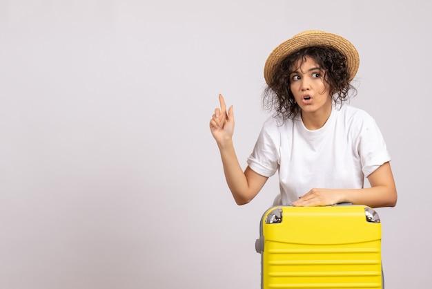 Vista frontale giovane donna con borsa gialla che si prepara per il viaggio su sfondo bianco colore volo resto viaggio aereo vacanza turistica