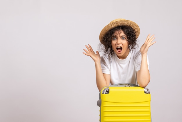 Front view young female with yellow bag preparing for trip on a white background color flight voyage vacation plane sun rest tourist