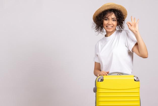 Vista frontale giovane donna con borsa gialla che si prepara per il viaggio su sfondo bianco colore vacanza viaggio volo aereo turistico rest