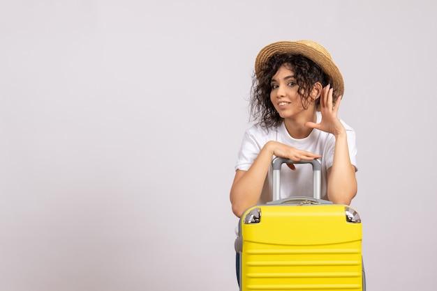 Vista frontale giovane femmina con borsa gialla che si prepara per il viaggio su sfondo bianco sole colore viaggio aereo resto vacanza volo turistico